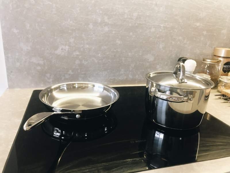 Готварски съдове от инокс върху индукционен кухненски плот на Bosch
